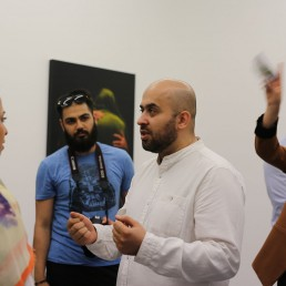 Ali Sabouki is talking with people in his exhibition